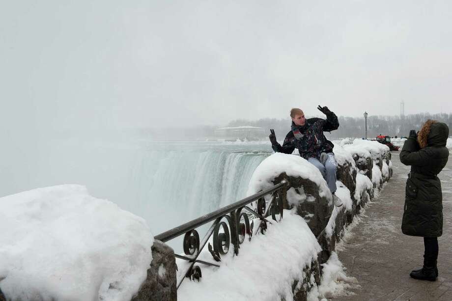 An adventuresome tourist flashes two hopeful peace signs as his photograph is taken near the arch of the horseshoe at Niagara Falls. Photo: Dino Chiecchi /For The Express-News
