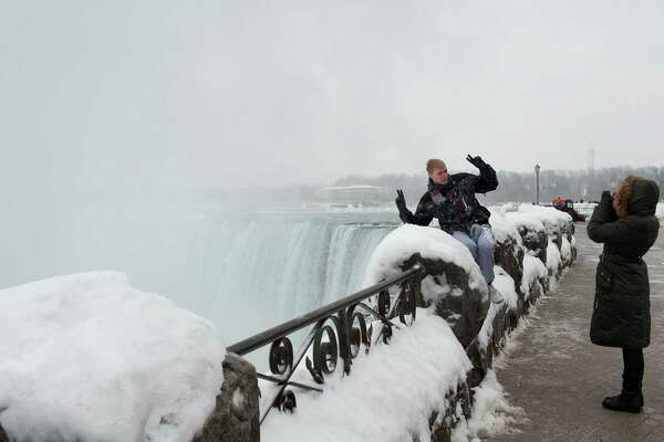 An adventuresome tourist flashes two hopeful peace signs as his photograph is taken near the arch of the horseshoe at Niagara Falls.