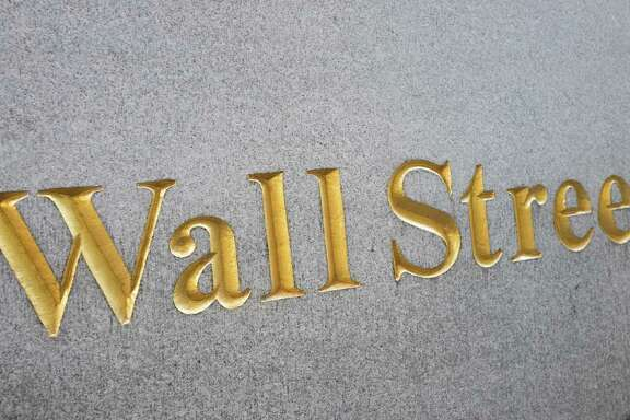 A sign for Wall Street is carved into a building located near the New York Stock Exchange, Friday, Oct. 7, 2016. Solid, if uninspiring,  U.S. stocks veered lower in early trading Friday, Oct. 21,  as investors pored through earnings from General Electric, McDonald's and other big companies. (AP Photo/Mark Lennihan)