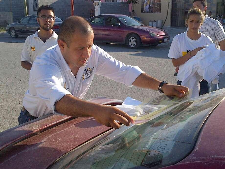Everardo Quiroz Torres, candidato a Presidente Municipal por el PRD, coloca una calcomanía de propaganda sobre el auto de un ciudadano en Nuevo Laredo, México. (Foto de cortesía)