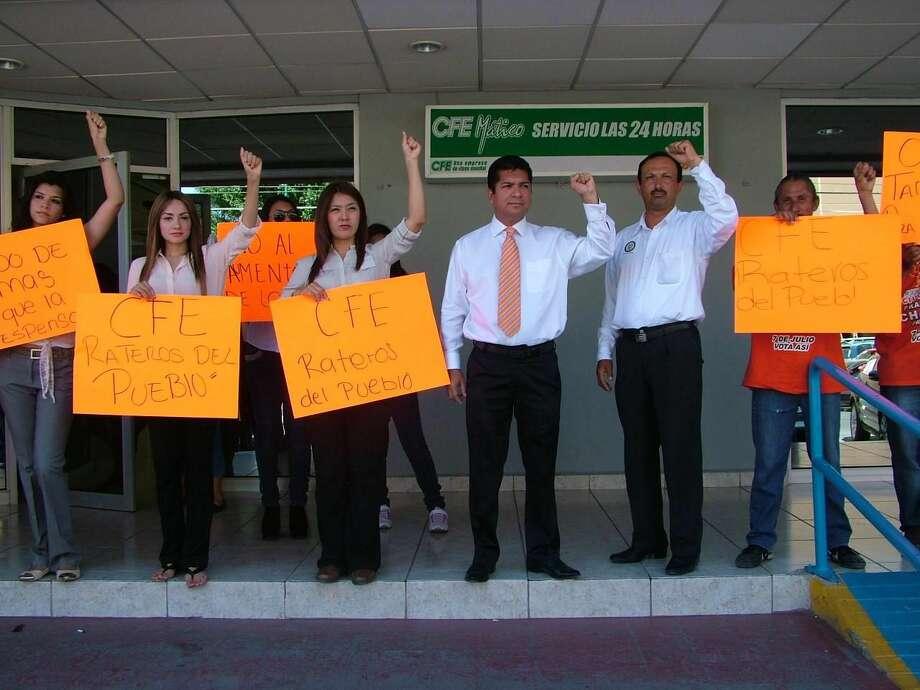 El candidato del partido Movimiento Ciudadano, a la Presidencia Municipal de Nuevo Laredo, México, Francisco Chavira Martínez, cuarto de izquierda a derecha, encabezó junto con los candidatos a Diputado Local por el MC, una protesta por las altas tarifas de luz frente a las oficinas de la CFE. (Foto de cortesía/MC)