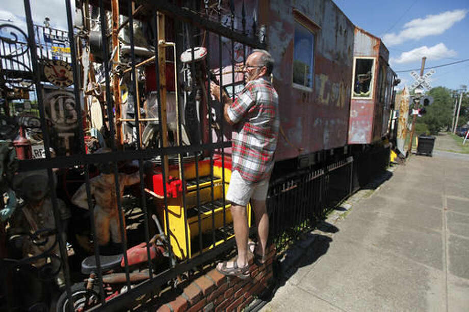 Don Kelsey uses his phone to take photos of Jerry Lotz' collection of antiques in Louisville, Ky. on Sept. 12, 2016. (Pat McDonogh/The Courier-Journal via AP)