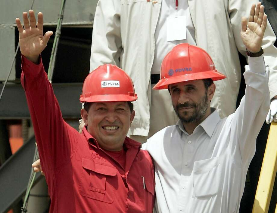 In this Sept. 18, 2006 file photo, Venezuela's President Hugo Chavez, left, and Iran's President Mahmoud Ahmadinejad wave to the press after inaugurating an oil drill in San Tome, Venezuela. (AP Photo/Fernando Llano, File)
