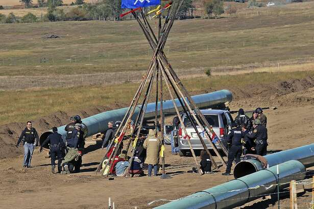 Law enforcement officers (left) drag a person from a protest against the Dakota Access Pipeline near the town of St. Anthony in rural Morton County, N.D. After years of focusing on the now fading coal industry, environmentalists are targeting pipelines as the new public enemy No. 1 — a strategy that has implications for Texas as home to several major pipeline companies.