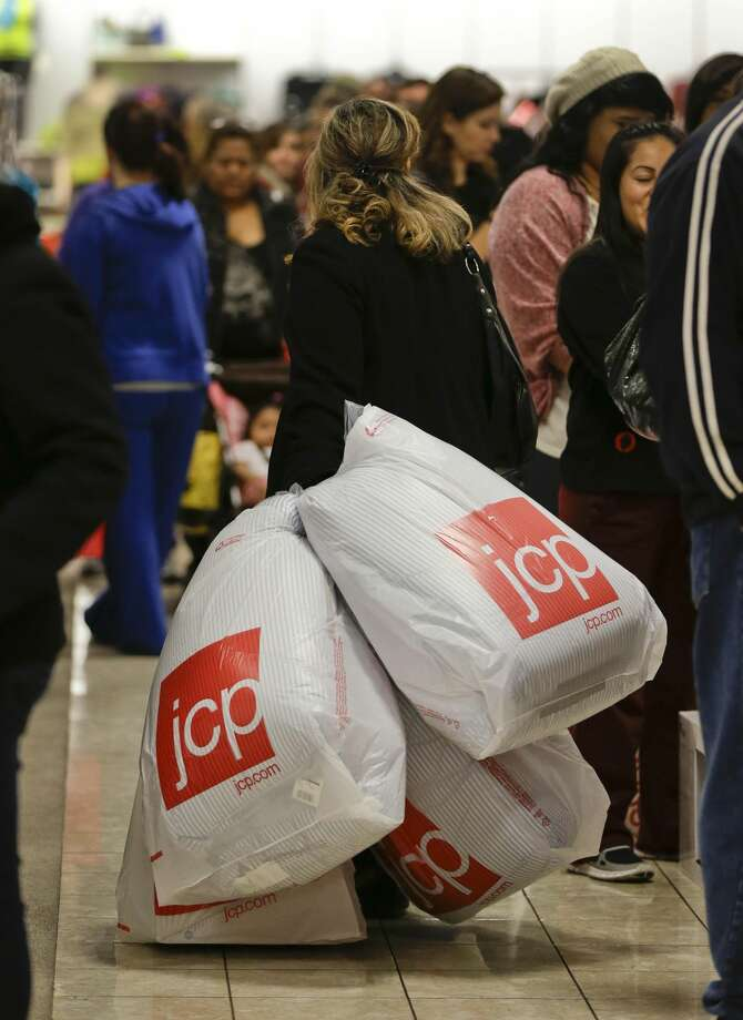 In this Friday, Nov. 23, 2012, file photo, a shopper drags her purchases past a line of customers waiting to pay at a J.C. Penney store, in Las Vegas. The mid-priced department store chain on Wednesday, Feb. 26. 2013 reported another much larger-than-expected loss in the fiscal fourth quarter and a nearly 30 percent plunge in revenue in the latest sign that shoppers aren't happy with the changes it's made in the past year. The results mark a full year of massive quarterly losses and revenue declines since J.C. Penney Co. began a turnaround strategy that included ditching most of its coupons and sales events in favor of everyday low prices, bringing in new designer brands such as Betsy Johnson and remaking outdated stores to give them an outdoor mall kind of feel. (AP Photo/Julie Jacobson, File)