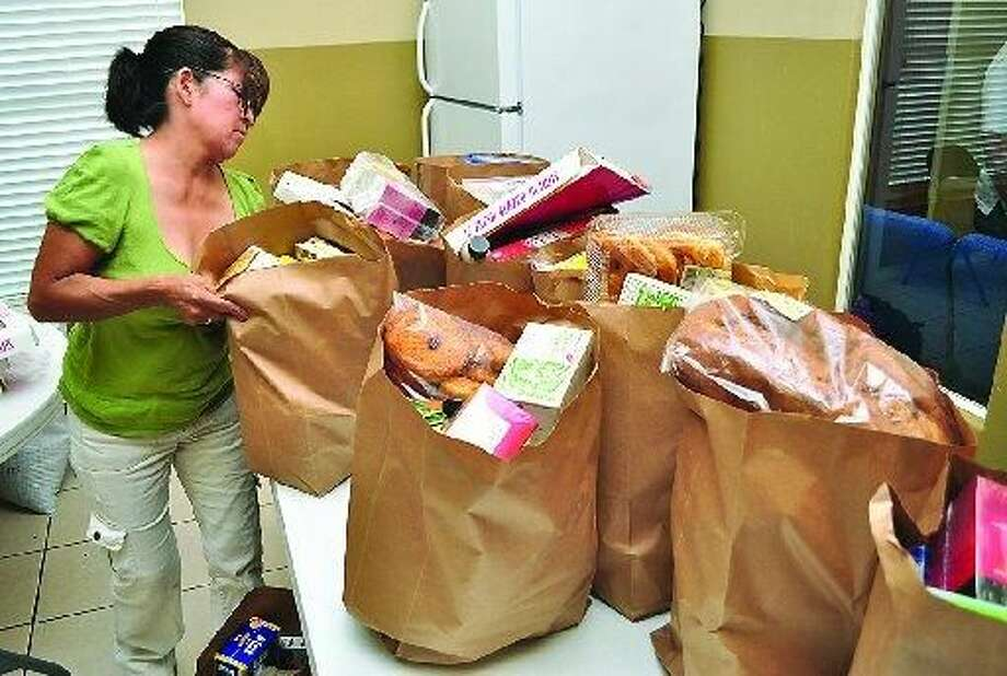 Ana Newsome, a volunteer at the New Vision Church prepares backgs of groceries to be distributed to the needy of the community.