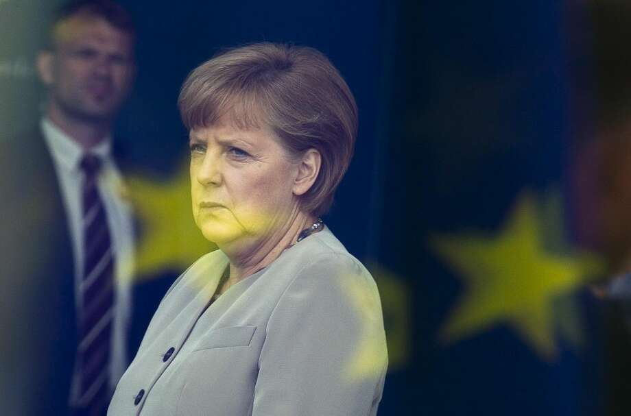The June 12, 2012 file photo shows German Chancellor Angela Merkel behind a window with a reflection of the European flag at the chancellery in Berlin, Germany. By rejecting an EU bailout and turning to Russia for help, Cyprus is exposing growing frustration and dwindling solidarity within a bloc that was meant to bring the continent closer together after World War II. The chaos over the rescue plan, which the Cypriot parliament roundly rejected Tuesday, has renewed many of doubts about the legitimacy of the European project _ notably over perceived German dominance and threats to national sovereignty. The extraordinary spectacle of an EU member seeking salvation from the old Cold War enemy has raised deep questions about how far Europe can and will go to take care of its own. (AP Photo/Markus Schreiber)
