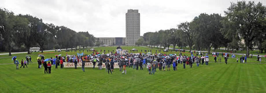 """People rally against the Dakota Access Pipeline on the grounds of the North Dakota state capitol Friday, Sept. 9, 2016 in Bismarck, N.D. The federal government stepped into the fight over the Dakota Access oil pipeline Friday, ordering work to stop on one segment of the project in North Dakota and asking the Texas-based company building it to """"voluntarily pause"""" action on a wider span that an American Indian tribe says holds sacred artifacts. (Tom Stromme/The Bismarck Tribune via AP)"""
