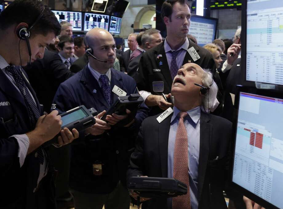 Peter Tuchman, right, works with fellow traders on the floor of the New York Stock Exchange Friday, March 15, 2013. U.S. stocks fell, ending the longest winning streak for the Dow Jones industrial average in nearly 17 years. (AP Photo/Richard Drew)