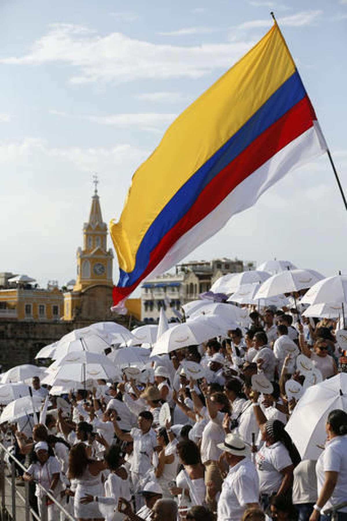 People wait for the start of the peace ceremony prior the signing of the peace agreement between Colombia's government and the Revolutionary Armed Forces of Colombia, FARC, in Cartagena, Colombia, Monday, Sept. 26, 2016. Colombia's government and the FARC will sign a peace agreement to end over 50 years of conflict. (AP Photo/Fernando Vergara)