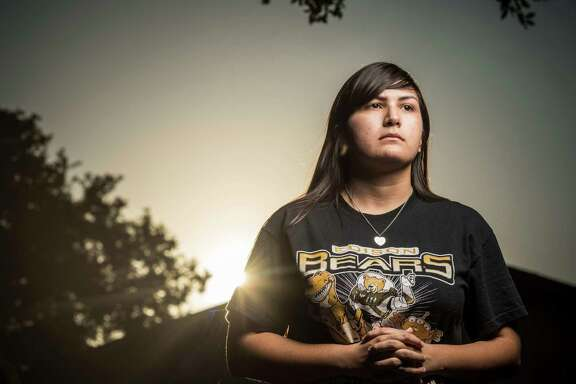 Mercedez Montemayor, a 17-year-old senior at Edison High School, poses; for a photo in front of her family's home in San Antonio. On Aug. 29, Mercedez was sitting in her car on West Avenue waiting to pick up a friend from work when a man approached her car and forced her at gunpoint into the passenger seat. Mercedez jumped out of the moving vehicle and ran to safety. The crime has marred Mercedez's senior year -- she no longer has a car, she has trouble sleeping and she's afraid to go out at night.