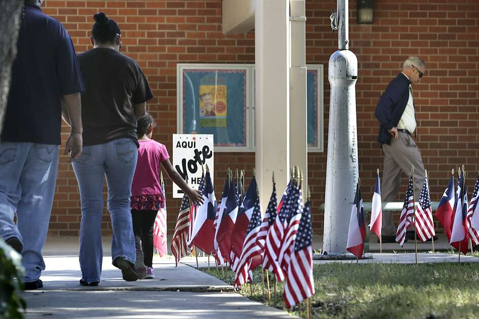 Voters are surrounded by a flag display on their way to vote on Tuesday, November 3, 2015, at Oak Grove Elementary School on Nacogdoches Rd.
