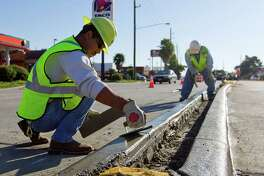 Workers smooth out concrete medians to improve traffic flow on Sawdust Road Friday in Spring.
