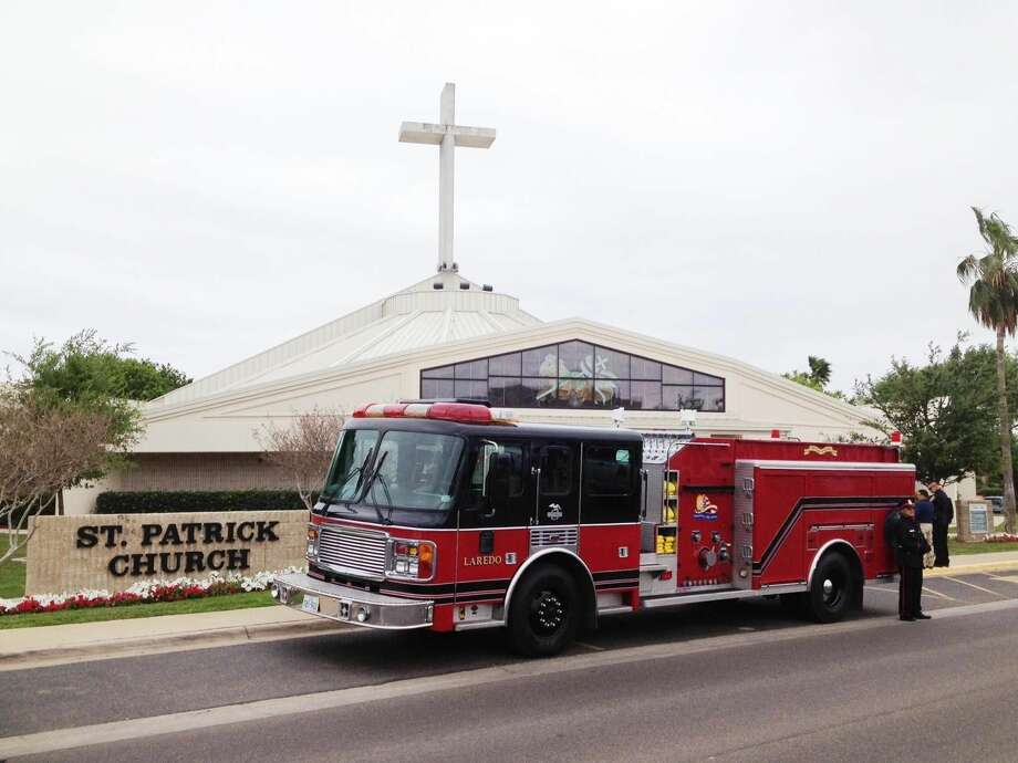 A Laredo Fire Department engine that carried the body of fire fighter Marcos Aranda is seen outside St. Patrick's Catholic Church Wednesday morning where a funeral mass was celebrated. (Photo by: Cuate Santos