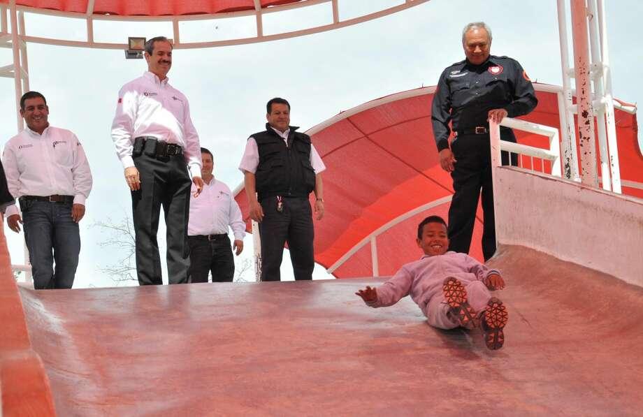 Funcionarios del Gobierno Municipal de Nuevo Laredo, México, observan conforme un niño utiliza el resbaladero tipo volcán que se ubica en el Parque Mendoza. (Foto de cortesía)