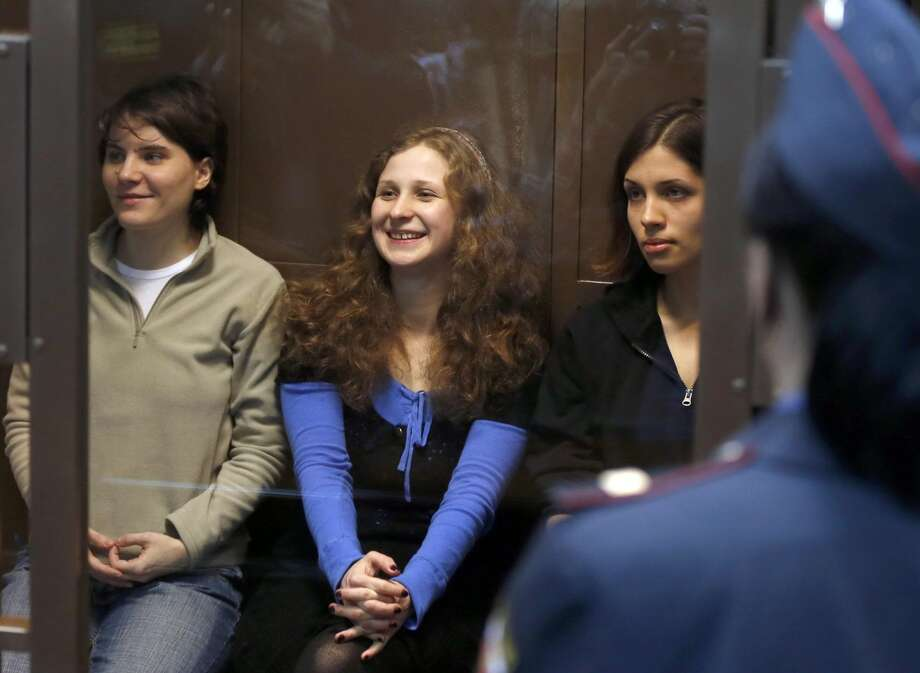 Feminist punk group Pussy Riot members, from left, Maria Alekhina, Yekaterina Samutsevich and Nadezhda Tolokonnikova sit in a glass cage at a court room in Moscow, Wednesday. Oct. 10, 2012. The Moscow City Court ruled Wednesday that Yekaterina Samutsevich's sentence should be suspended because she was thrown out of the cathedral by guards before she could remove her guitar from its case and thus did not take part in the performance. (AP Photo/Sergey Ponomarev)