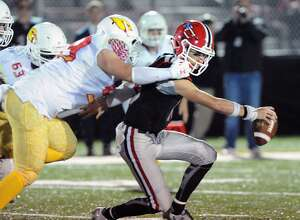 Greenwich's Sam Colandro, left, tackles New Canaan quarterback Drew Pyne during the second quarter of their game Friday night at New Canaan High.