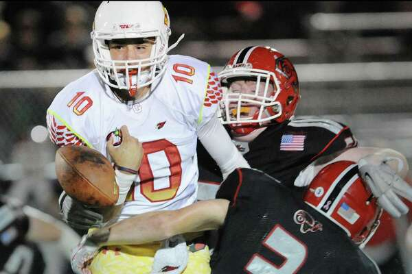 A hit by New Canaan's Grant Morse (#3), right, and teammate, Seamus O'Hora, background, causes Greenwich quarterback Connor Langan (#10) to fumble during second quarter action of the high school football game between Greenwich High School and New Canaan High School at New Canaan, Conn., Friday night, Oct. 21, 2016.