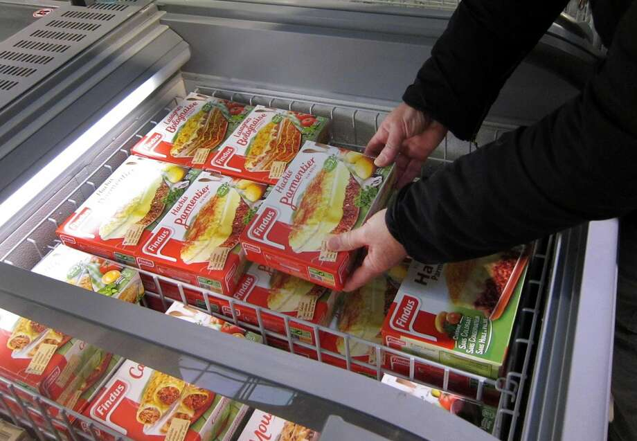In this Feb. 11, 2013 file photo, a customer takes a pack of frozen beef Hachis Parmentier from a freezer in a supermarket in Nice, southeastern France. The Europe-wide uproar over fraudulently labeled horse meat, sold as beef, has exposed the labyrinthine path of companies and countries across the continent that meat for prepared dishes takes before it reaches that microwave. But the back story reveals a France as dependent on factory food as other nations, and a people increasingly torn between their heritage and their hectic lives. (AP Photo/Lionel Cironneau, File)
