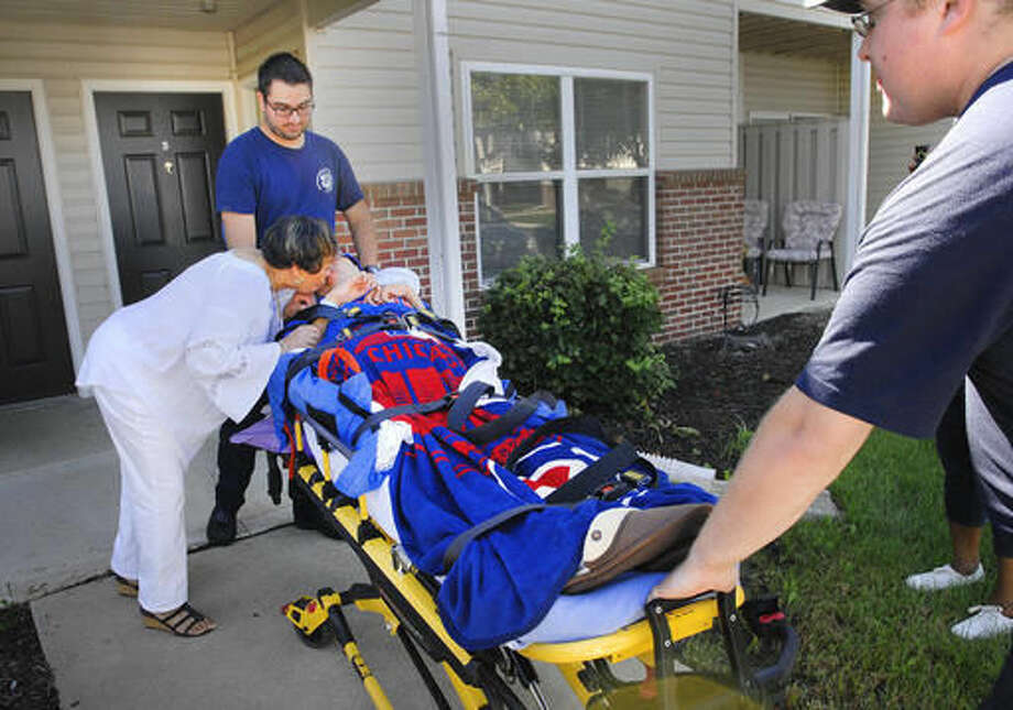 In this Sept. 19, 2016 photo, LeRoy Emergency Medical Technicians Chris Dunning and Kyle Moulten wheel Norman Wilson into a waiting ambulance as his mother, Gerri Wilson, kisses him goodbye at their home in Bloomington, Ill., before the EMTs take him to a Chicago Cubs baseball game. The EMTs and paramedics/firefighters had worked with the Cubs to reserve space for Wilson and a reclining stretcher in the left field bleachers at Wrigley Field. That way, he could watch the Central Division Champions with his friends, the EMTs. (David Proeber/The Pantagraph via AP)