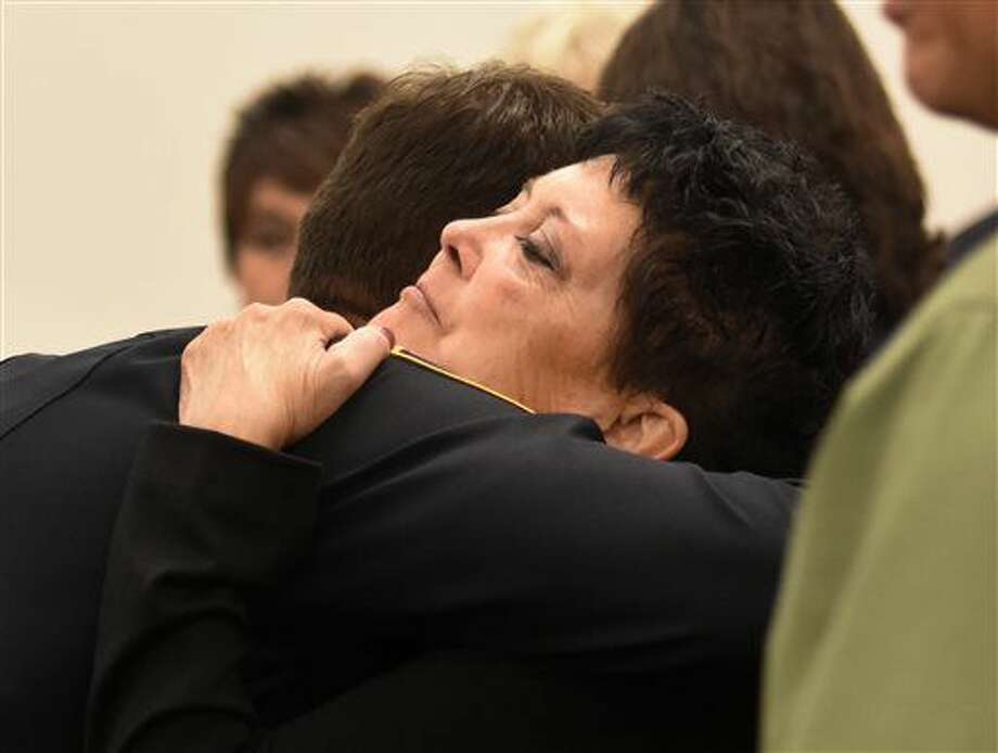 Julie Benner, widow of police officer Gregg Benner, is given support by members of the Rio Rancho Police Department, during the first day of testimony of a trial in Los Lunas, N.M., for suspect Andrew Romero, Thursday, Sept. 8, 2016. Law enforcement officers and the widow of the police officer shot and killed after making a traffic stop in an Albuquerque suburb last year watched in tears Thursday as prosecutors showed jurors video of emergency workers trying to render life-saving aid to him. (Dean Hanson/The Albuquerque Journal via AP)