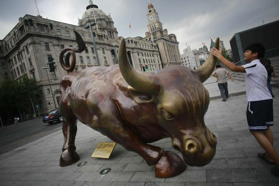 A visitor touches Italian-American artist Arturo Di Modica's new Charging Bull statue, which is a similar version of his Wall Street Bull Thursday Aug. 30, 2012 in Shanghai, China. (AP Photo/Eugene Hoshiko)