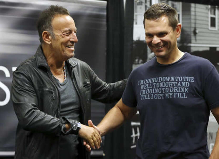 "Bruce Springsteen, left, greets a fan wearing a shirt with a Springsteen lyric, at the launch of his autobiography ""Born to Run"" at the Barnes & Noble in the New Jersey town where he grew up Tuesday, Sept. 27, 2016, in Freehold, N.J. (AP Photo/Mel Evans)"