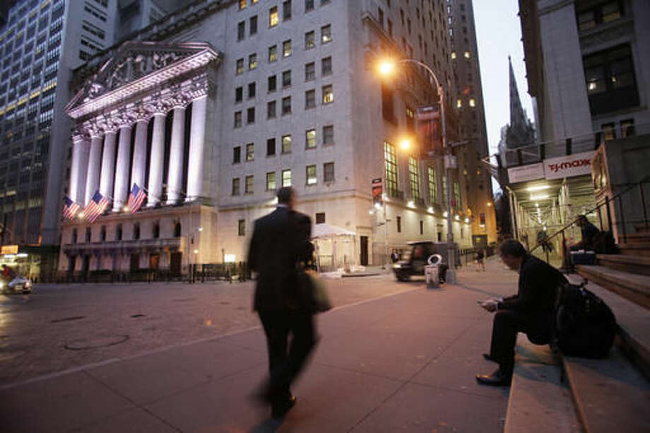 FILE - In this Oct. 8, 2014, file photo, a man walks to work on Wall Street, near the New York Stock Exchange, in New York. Global stock markets tumbled Monday, Sept. 12, 2016, as investors fretted over the possibility of an imminent U.S. interest rate hike and reacted to the weekend health problems of presidential candidate Hillary Clinton. (AP Photo/Mark Lennihan, File)