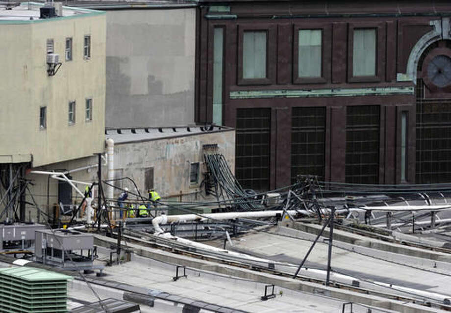 Workers examine a section of the roof at the Hoboken station where a train crashed into the building, Thursday Sept. 29, 2016 in Hoboken, N.J. A rush-hour commuter train crashed through a barrier at the busy Hoboken station and lurched across the waiting area Thursday morning, killing one person and injuring more than 100 others in a tangle of broken concrete, twisted metal and dangling wires. (AP Photo/Joe Epstein)