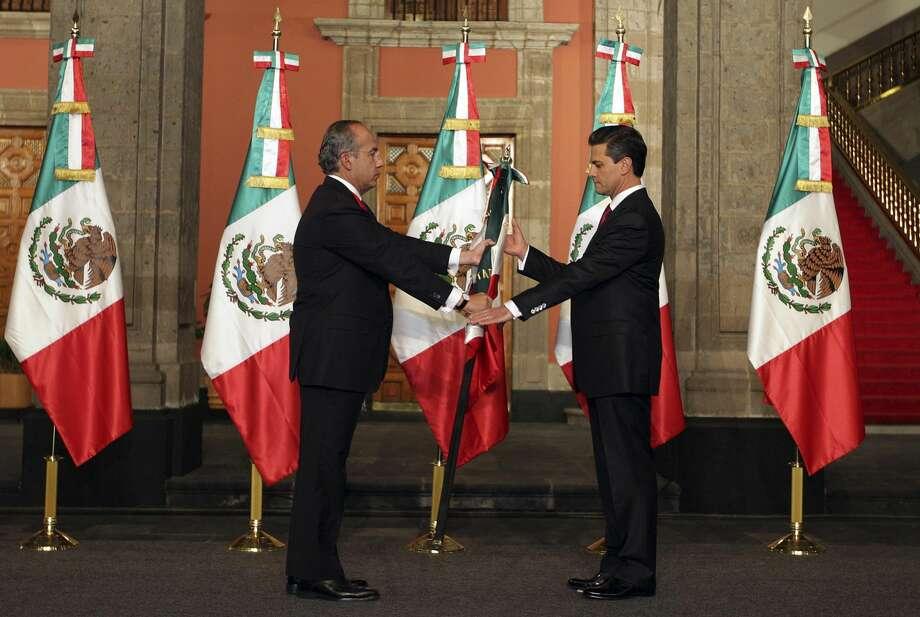 Momento cuando el Presidente Enrique Peña Nieto recibe la bandera mexicana de manos del mandatario saliente Felipe Calderón, el 1 de diciembre. Peña Nieto anunció su estrategia de seguridad el lunes.(Foto AP/Oficina de Prensa del presidente electo Enrique Peña Nieto)