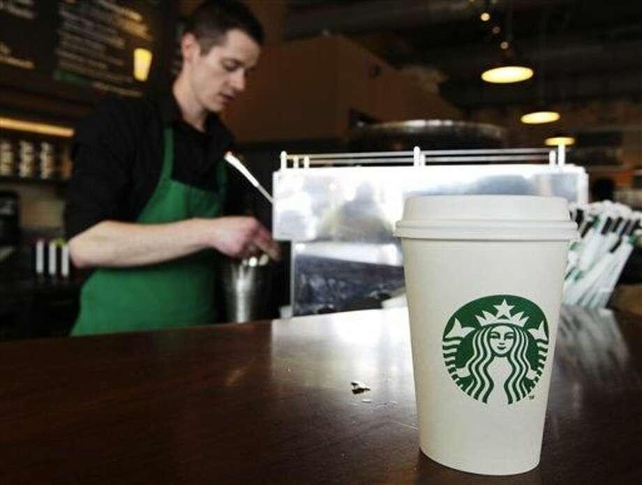 """Un vaso de la cafetería Starbucks ha sido servido para un cliente mientras el empleado Josh Barrow prepara otro en un establecimiento de la firma en Seattle, Washington, el viernes 27 de abril de 2012. Starbucks, la cadena de cafeterías más grande del mundo, solicitó a los empleados de la zona de Washington, D.C., que escriban en los vasos las palabras """"Come Together"""" (Unanse) en referencia a la necesidad de que la Casa Blanca y el Congreso alcancen un acuerdo que evite el llamado """"precipicio fiscal"""". (AP Foto/Ted S. Warren)"""