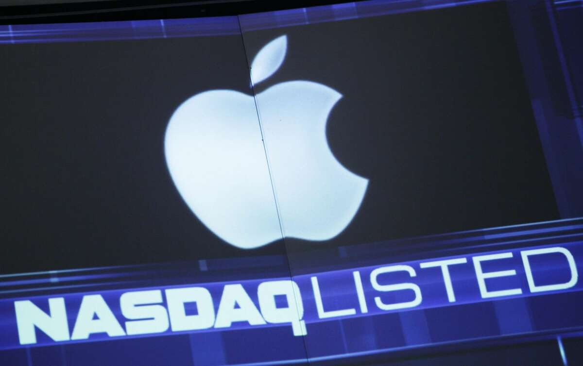 In this Tuesday, Aug. 21, 2012, file photo, the Apple logo is shown on a stock ticker at the Nasdaq MarketSite, in New York. Apple is entering the home stretch of what will likely be its best holiday season yet as shoppers snap up iPhones and iPads in record numbers in December 2012. Yet the world's most valuable company has lost its luster among investors, causing Apple's stock price to plunge by more than 20 percent from a peak reached less than three months ago when the latest iPhone went on sale. (AP Photo/Mark Lennihan)