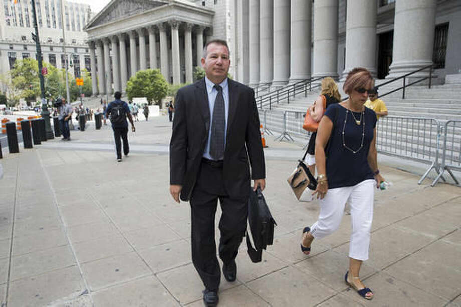 """In this July 13, 2016 photo, retired New York Police Department Sgt. Ronald Buell, center, leaves federal district court in Manhattan. Buell received probation for selling National Crime and Information Center information to a private investigator for defense attorneys. At his sentencing, Buell said he hoped other officers would learn """"to never put themselves in the position I'm in."""" (AP Photo/Mary Altaffer)"""