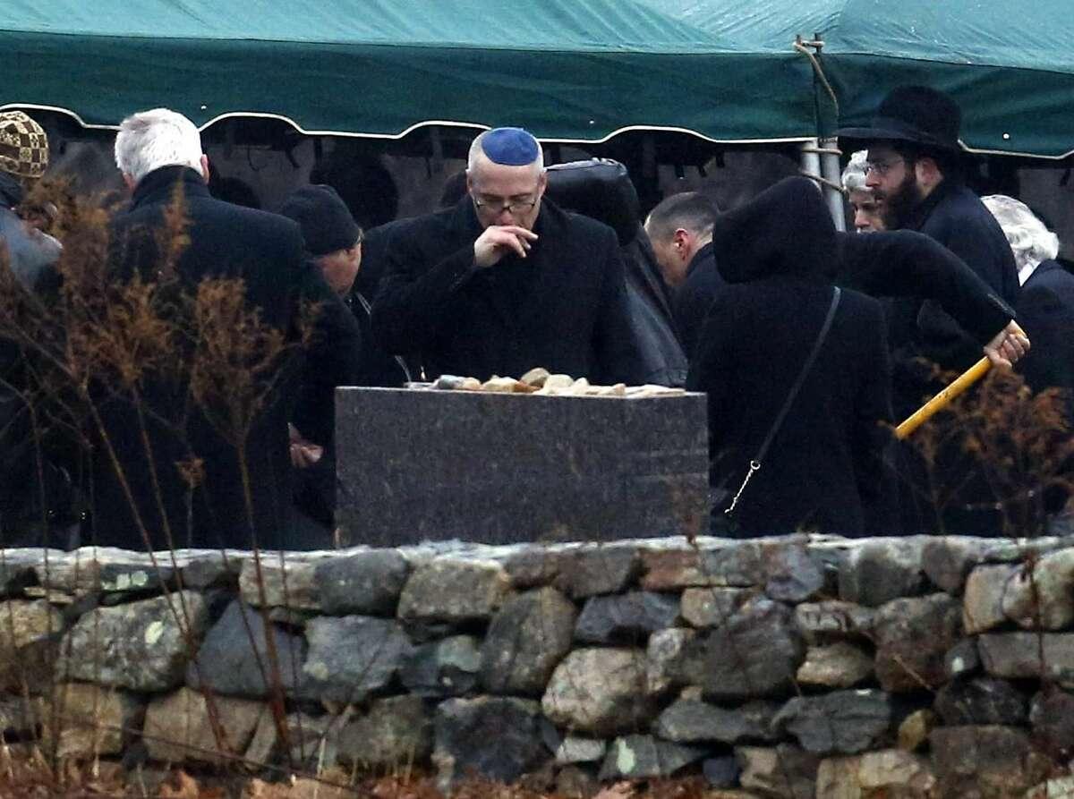 Un hombre solloza mientras otros arrojan tierra sobre la tumba de Noah Pozner, un niño de seis años asesinado en la matanza de la primaria Sandy Hook, durante el entierro en el cementerio B'nai Israel de Monroe, Connecticut, el lunes. (Foto AP/Julio Cortez)