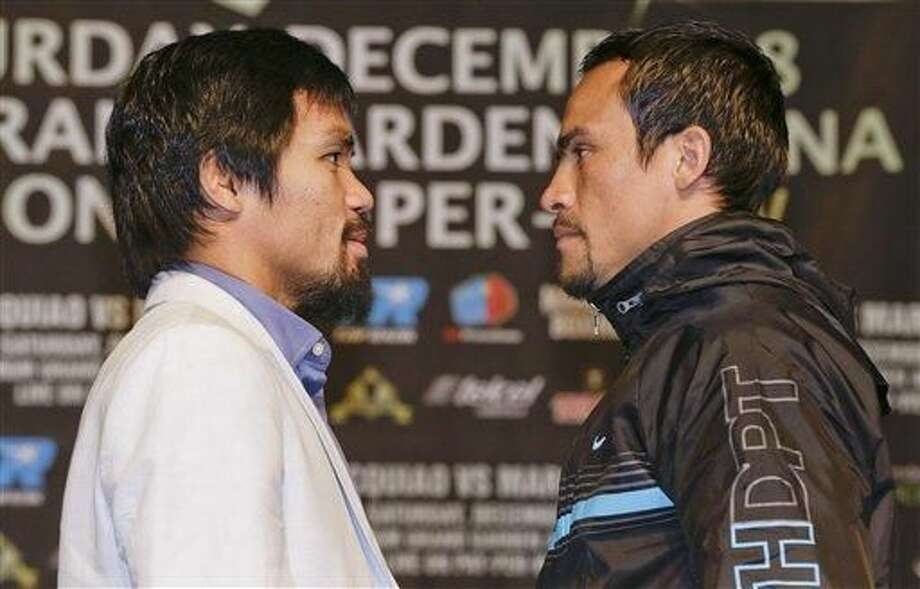Manny Pacquiao, izquierda, y Juan Manuel Márquez posan para fotos durante una conferencia de prensa ewl miércoles, 5 de diciembre del 2012, en Las Vegas. Pacquiao y Márquez van a enfrentarse por cuarta vez el sábado. (Foto AP/Julie Jacobson)