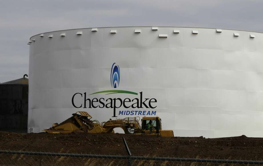 In this May 16, 2011 file photo, earth-moving machinery builds up a berm around a Chesapeake Energy storage tank, near Dilley, Texas. The Oklahoma City-based company is selling the vast portion of its land and infrastructure in west Texas for nearly $7 billion as it unloads debt and shifts more of its focus to drilling for oil, rather than natural gas. (AP Photo/Pat Sullivan, File)