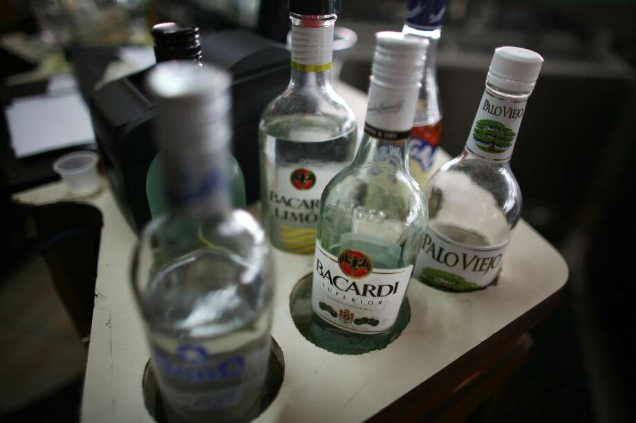 In this Friday, Sept. 7, 2012, file photo, a variety of Puerto Rican rums sit at a bar in San Juan, Puerto Rico, Friday, Sept. 7, 2012. Small producers in countries such as Antigua, Guyana and Jamaica complain they are being punched by unfair trade and marketing advantages for global beverage corporations operating in U.S. territories, and say U.S. rum subsidies threaten to drive some beloved top-shelf Caribbean labels out of business, or force them to sell out. (AP Photo/Ricardo Arduengo)