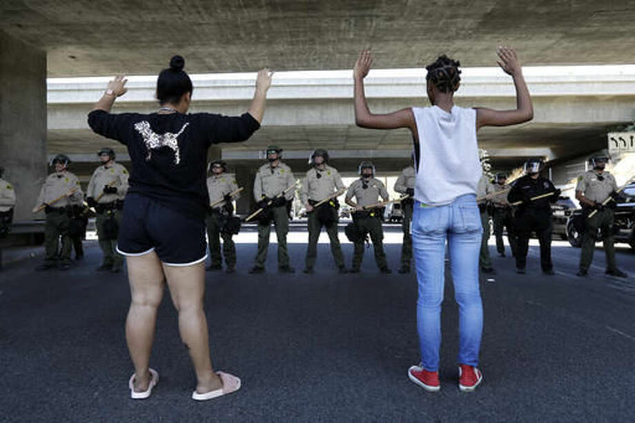 """Two women raise their hands in front of a line of police during a protest Wednesday, Sept. 28, 2016, in El Cajon, Calif. Dozens of demonstrators on Wednesday protested the killing of a black man shot by an officer after authorities said the man pulled an object from a pocket, pointed it and assumed a """"shooting stance."""" (AP Photo/Gregory Bull)"""