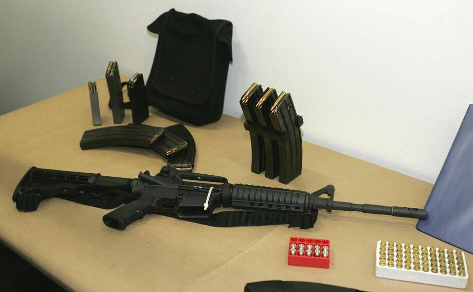 This March 27, 2006 file photo, shows a Bushmaster AR-15 semi-automatic rifle and ammunition on display at the Seattle Police headquarters in Seattle. The maker of the Bushmaster rapid-fire weapon used to kill schoolchildren in Connecticut on Friday, Dec. 14, 2012, was put up for sale on Tuesday, Dec. 18, 2012, as investors soured on the gun business. (AP Photo/Ted S. Warren, File)