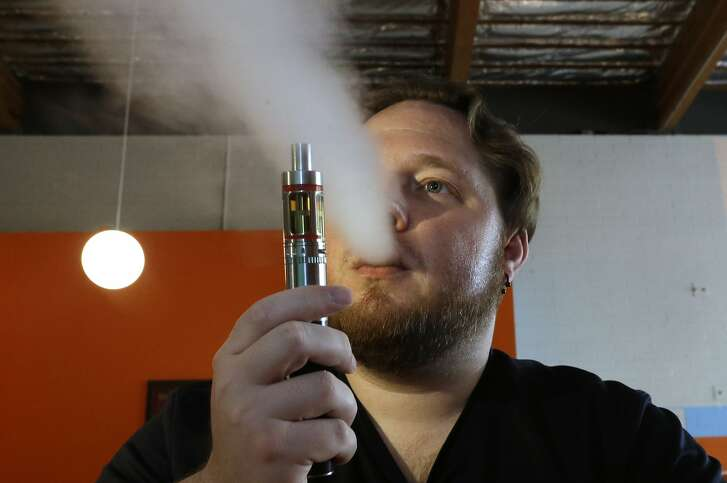 HOLD FOR STORY File - In this July 16, 2015 file photo, Bruce Schillin exhales vapor from an e-cigarette at the Vapor Spot, in Sacramento, Calif. Gov. Jerry Brown faces a midnight deadline to act on six bills to restrict tobacco use in California, including one to raise the legal age to buy tobacco for smoking, dipping, chewing and vaping from 18 to 21. (AP Photo/Rich Pedroncelli, File)