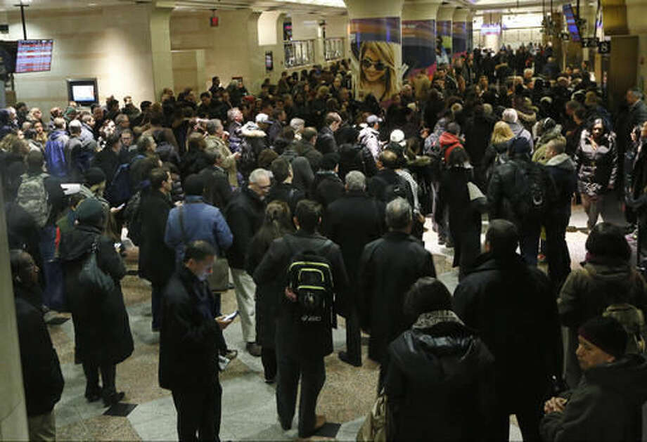 FILE- In this Jan. 6, 2016 file photo, commuters and travelers wait for their trains in side New York City's Penn Station. Plans are in place for the long-awaited renovation of the country's busiest rail station. They include widening concourses, raising ceilings and creating a sparkling, light-filled waiting area across the street from the dreary facility below New York's Madison Square Garden. (AP Photo/Kathy Willens, File)
