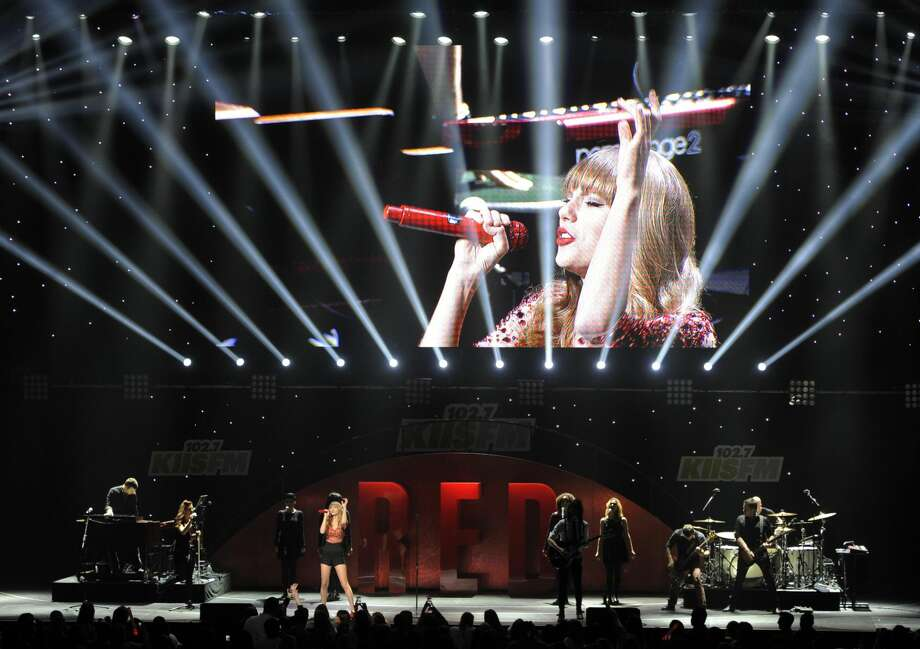 This Dec. 1, 2012 file photo shows Taylor Swift performing underneath a video monitor during the KIIS FM's Jingle Ball at Nokia Theatre LA Live in Los Angeles. Swift is one of many artists performing at the Grammy Nominations concert airing Wednesday, Dec. 5, at 10 p.m. EST on CBS. (Photo by Chris Pizzello/Invision/AP, file)