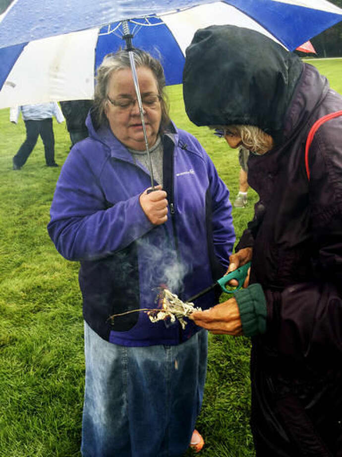 """Darlene Pipeboy, right, from the Lake Traverse Reservation in South Dakota, burns sage grass during a rally of Dakota Access pipeline protesters at the North Dakota Capitol grounds Friday, Sept. 9, 2016, in Bismarck. Pipeboy says the Native American custom """"restores balance in all things."""" Pipeboy was among hundreds of protesters at the Capitol who cheered wildly when it was announced that federal officials are asking that construction on part of the pipeline be temporarily shut down. Protesters carried signs that read """"Respect Our Water"""" and """"Water Is Sacred."""" (AP Photo/Blake Nicholson)"""