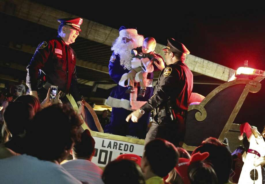 "The Laredo Police Department's Blue Santa holds an infant for a photo during the ""Light the Way for Christmas"" event at North Central Park on Wednesday evening. (Photo by Victor Strife/Laredo Morning Times)"