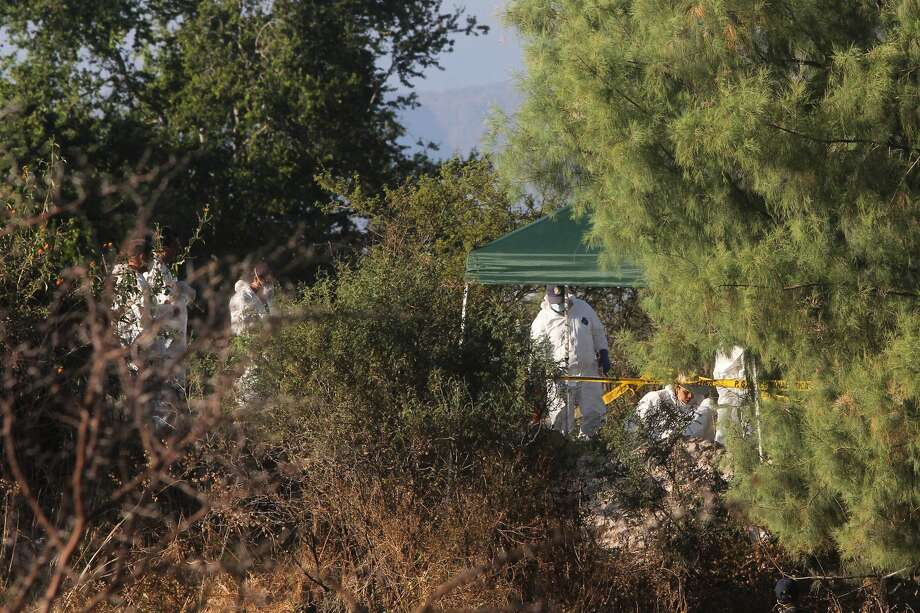 Forensic workers continue their search for bodies after several clandestine graves were found near the town of La Barca, western Mexico, Monday, Nov. 25. The number of bodies found in almost two dozen clandestine graves at the site has risen to 42, after five more corpses were discovered over the weekend. Agents were led to the 22 mass graves by local police officers who confessed to working with a drug cartel. (AP Photo)