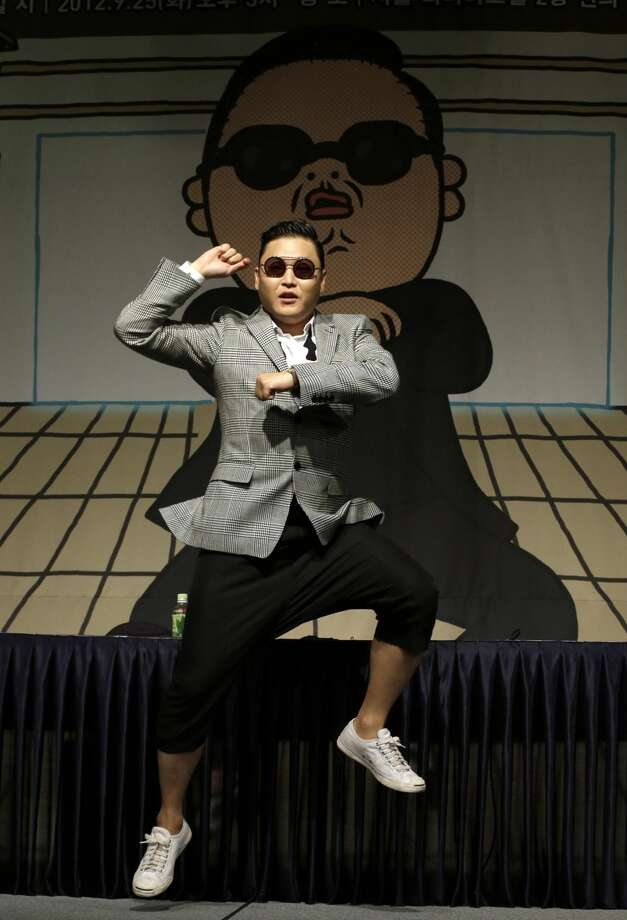 """South Korean rapper PSY, who sings the popular """"Gangnam Style"""" song, dances after his press conference in Seoul, South Korea, Tuesday, Sept. 25, 2012. (AP Photo/Lee Jin-man)"""