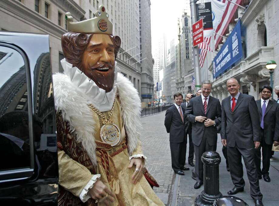 "In this May 18, 2006 photo, Burger King CEO John W. Chidsey, background center, watches as ""The King"" mascot of Burger King Corp. arrives at the New York Stock Exchange in New York. Burger King's spooky ""The King"" mascot is retiring so the struggling burger chain can refocus its marketing to reach new customers. The mascot has been around for years, but recently has become a more prevalent and somewhat creepy presence in ads. The fast food chain, which has suffered declining sales, will roll out a new advertising campaign that will focus on its burgers. (AP Photo/Richard Drew/file)"