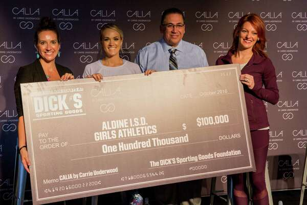IMAGE DISTRIBUTED FOR DICK'S SPORTING GOODS - CALIA by Carrie Underwood in partnership with The DICK'S Sporting Goods Foundation's Sports Matter program surprises unsuspecting athletes and coaches of the Aldine Independent School District with a $100,000 check donation at the DICK'S Sporting Goods Grand Opening Celebration at Baybrook Mall in Friendswood, TX on Friday, October 21, 2016. (Photo by Scott Dalton/Invision for DICK'S Sporting Goods/AP Images)