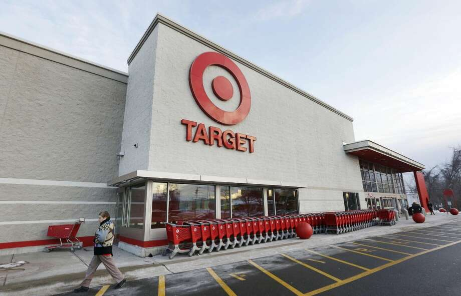 A passer-by walks near an entrance to a Target retail store in Watertown, Mass., on Thursday, Dec. 19. Target on Friday said that customers' encrypted PIN data was removed during the data breach that occurred earlier this month. But the company says it believes the PIN numbers are still safe because the information was strongly encrypted. (AP Photo/Steven Senne, File)