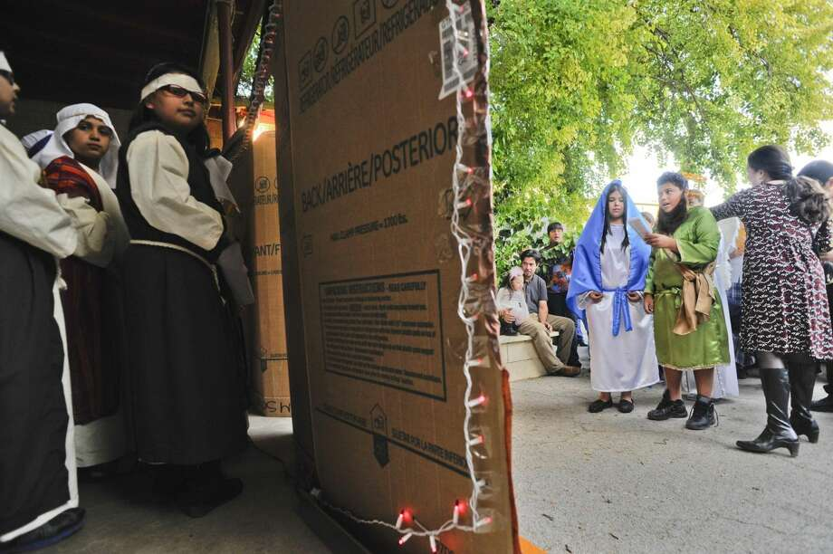 Students of St. Peter's Memorial School stand in and around a cardboard home in the Gran Posada Procession during a reenactment of Mary and Joseph's search for lodging, Tuesday afternoon at St. Peter's Memorial School. (Photo by: Danny Zaragoza